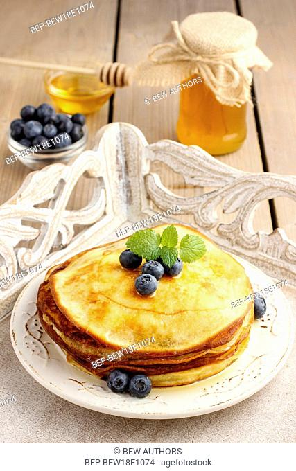 Stack of pancakes with syrup and blueberries. Summer party dessert