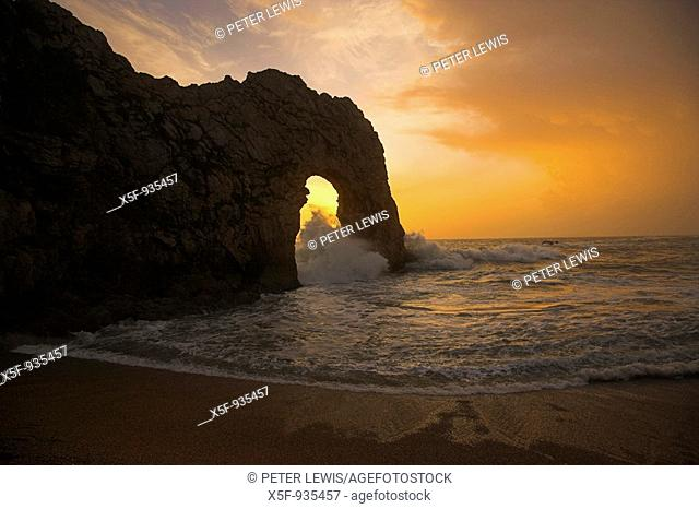 Sun setting through Durdle Door during rough weather and stormy Sea