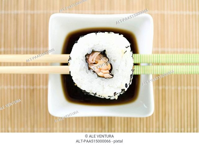 Maki sushi resting on chopsticks above soy sauce, overhead view