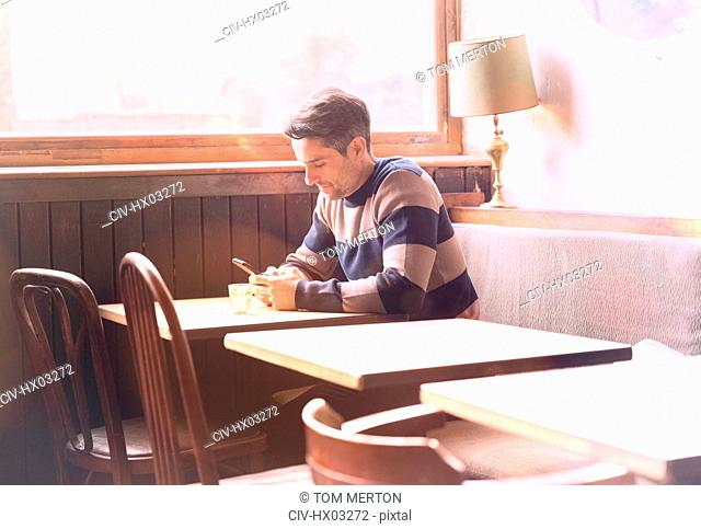 Man texting with cell phone at table in sunny cafe window