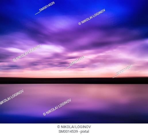 Horizontal vivid pink purple river sunset with reflection horizon landscape cloudscape background abstraction slow shutter