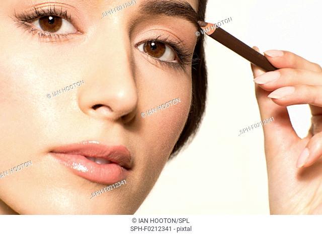 Woman applying eyebrow pencil