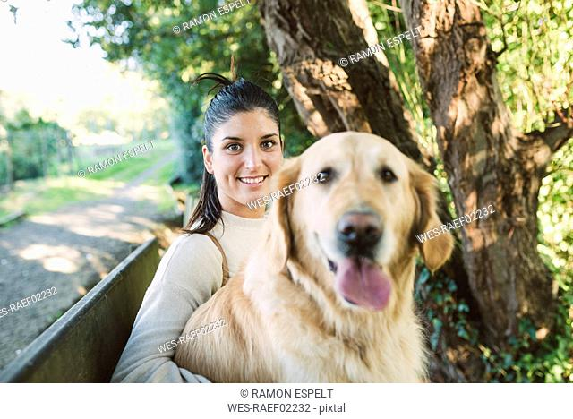 Portrait of a smiling young woman with her Golden retriever dog