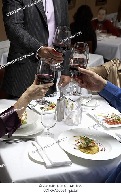 People toasting each other in restaurant