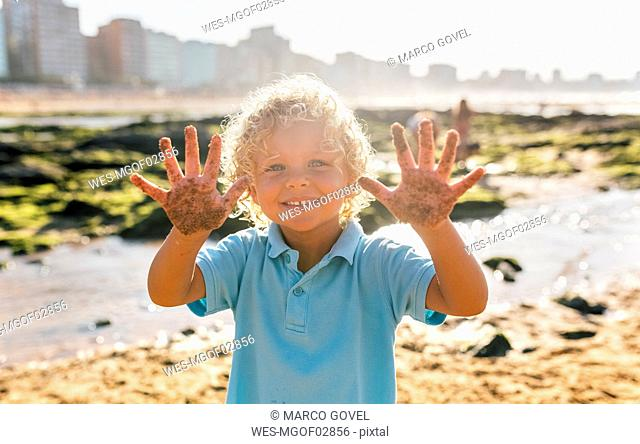 Portrait of smiling little boy showing his sandy hands on the beach