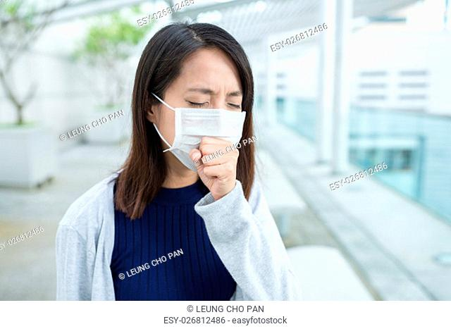 Woman feeling sick and wearing face mask