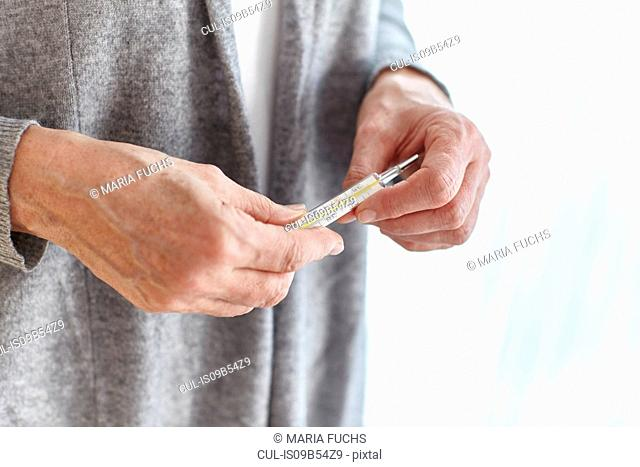 Senior woman holding thermometer, mid section