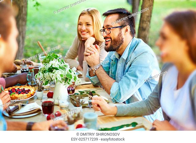 Happy Asian man in eyeglasses and casualwear sitting by Thanksgiving table