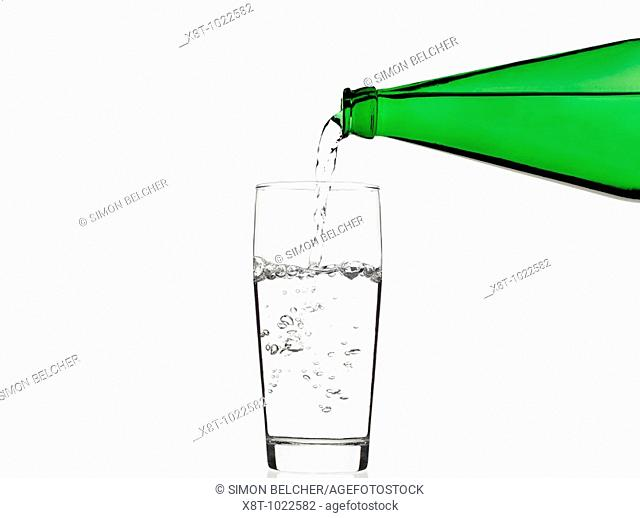 Pouring Water into a Glass Against a White Background