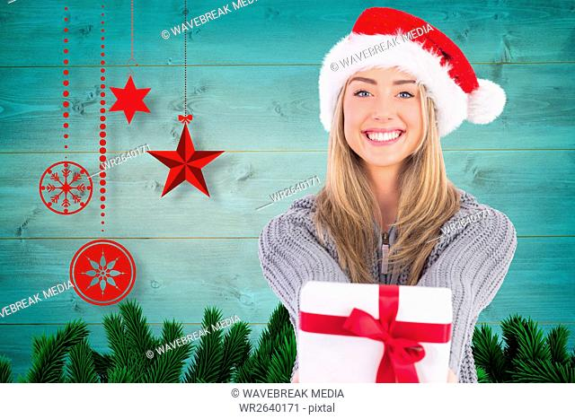 Smiling woman in santa hat holding gift against digitally generated christmas background