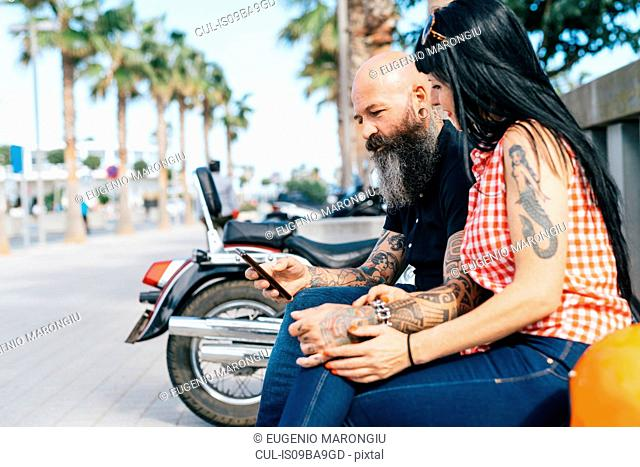 Mature hipster couple on bench looking at smartphone, Valencia, Spain