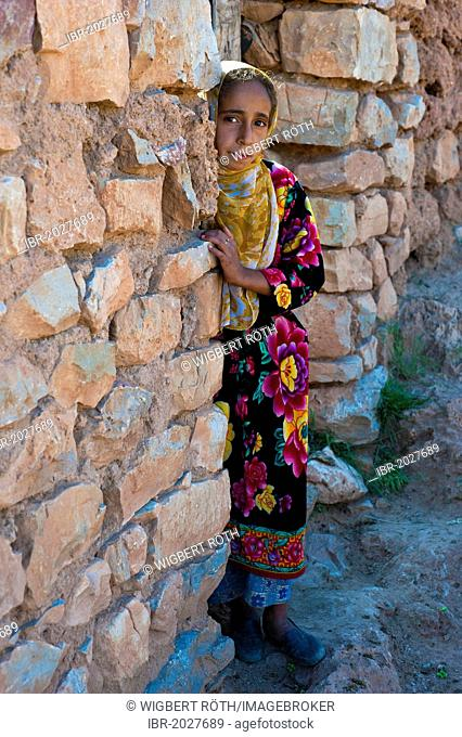 Young girl, berberine, looking curiously from behind a wall, Middle Atlas Mountains, Morocco, Africa