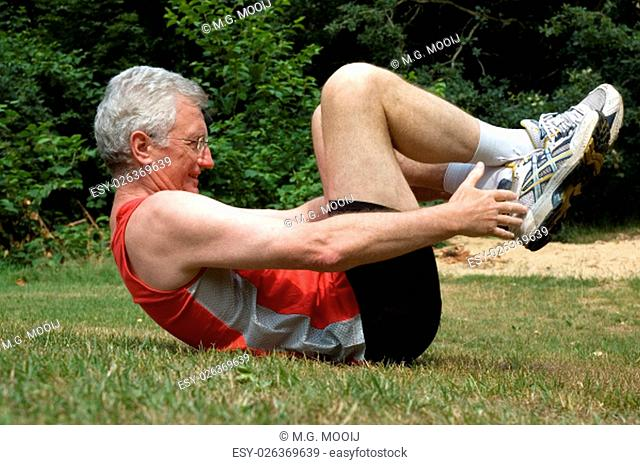 A senior man is stretching after a long run