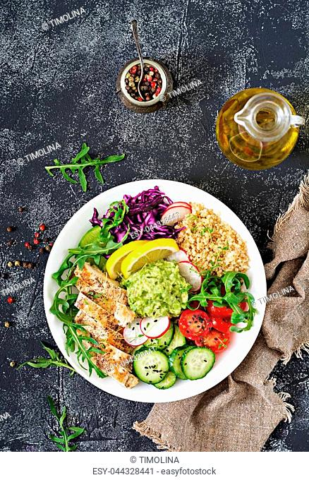 Healthy dinner. Buddha bowl lunch with grilled chicken and quinoa, tomato, guacamole, red cabbage, cucumber and arugula on gray background. Flat lay