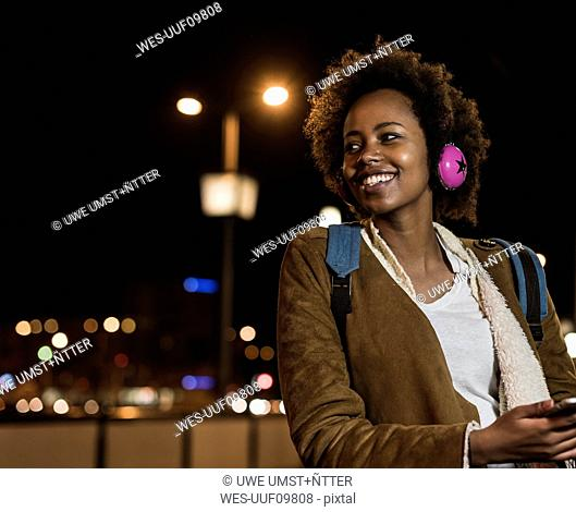 Portrait of smiling young woman with headphones waiting at the tram stop
