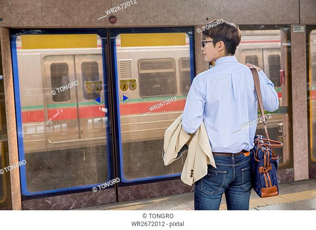 Back of businessman waiting for train