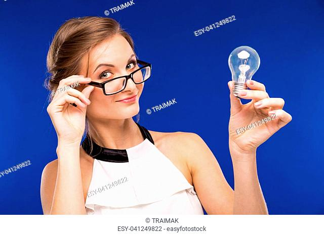 girl in glasses with a light bulb in his hands on a blue background