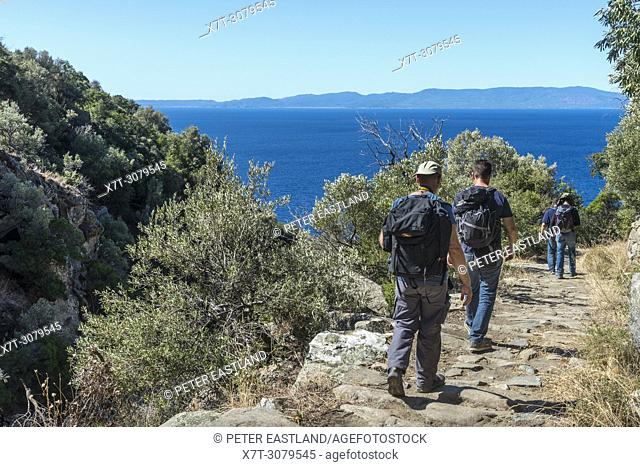 Walkers on a path between Xeropotamou and St. Panteleimon monasteries on The Southwest coast of the Athos peninsula, Macedonia, Northern Greece