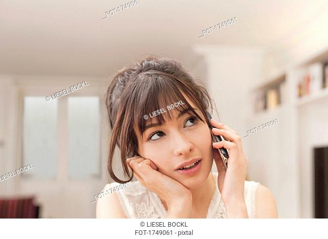 Young woman looking away while talking on mobile phone at home