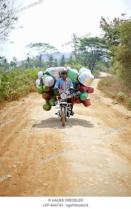 Peddler with water containers on a motorbike passing a road to Kabini, Karnataka, India