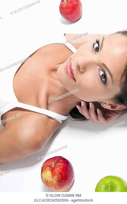 Close-up of a woman lying with red and green apples