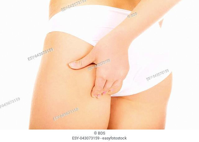 Slim young woman pinching her buttocks