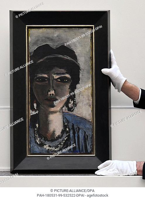 """31 May 2018, Germany, Berlin: An employee at Villa Grisebach holding the paiting """"""""Die Aegypterin"""""""" (lit. The Egyptian Woman)by Max Beckmann on a pedestal..."""