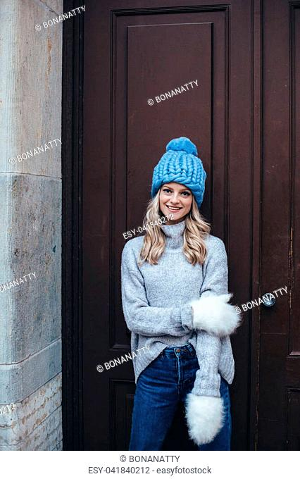 Young blonde woman in blue knitted hat, white fluffy mittens, grey sweater and blue jeans make posing with wooden door on the background