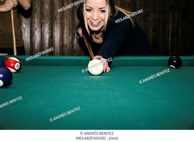 Woman playing pool billard in a bar, smiling