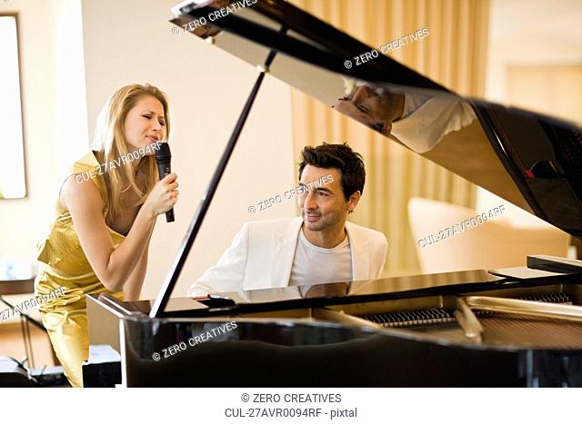Couple singing and playing piano
