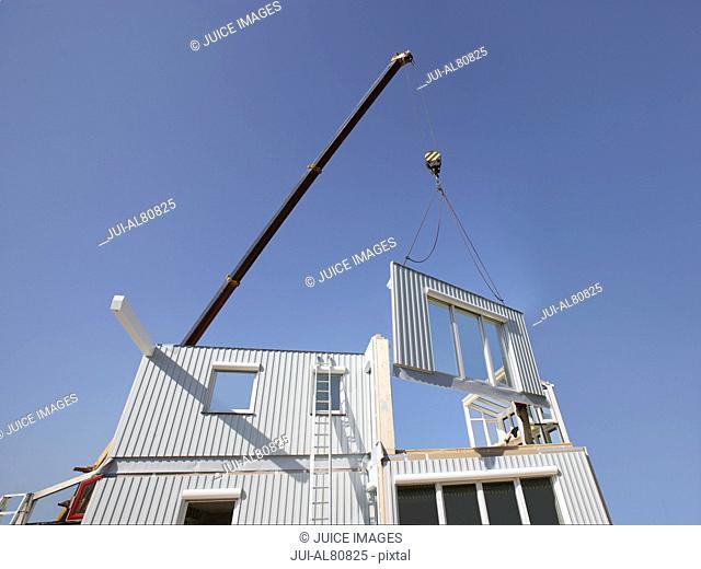 Crane assembling pieces of a house