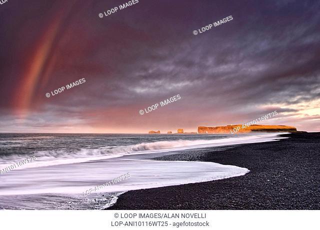 Rainbow over Reynisfjara volcanic black sand beach backed by Dyrholaey Island and Dyrholaeyjarviti lighthouse
