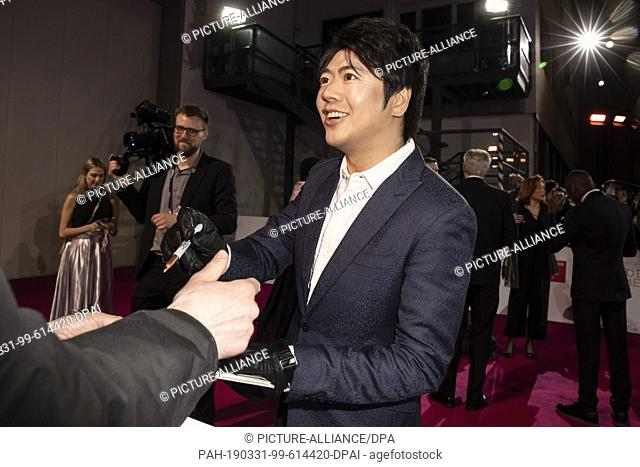 30 March 2019, Berlin: Lang Lang, pianist, signs autographs on the red carpet before the Golden Camera awards ceremony at Berlin's disused Tempelhof Airport