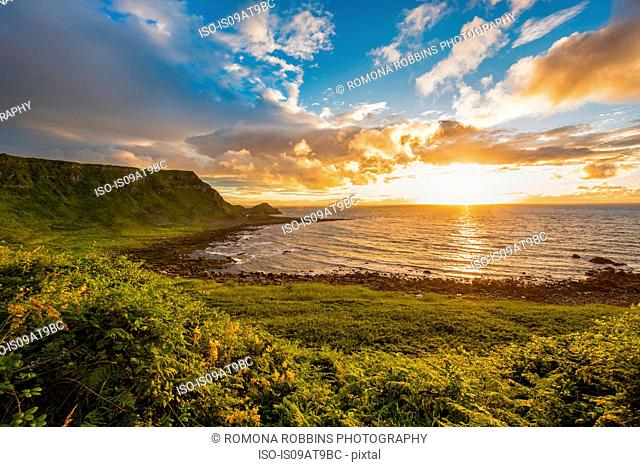 Sun setting on horizon over ocean, Giants Causeway, Bushmills, County Antrim, Ireland, UK