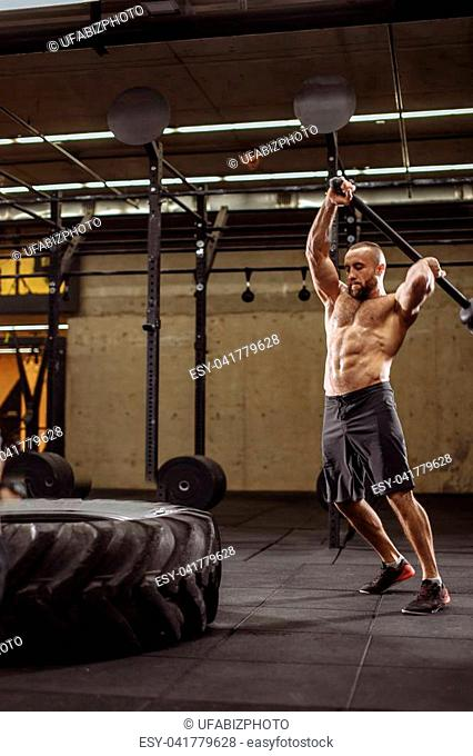 strong bodybuilder ia making great efforts to hit the tractor tire. full length portrait