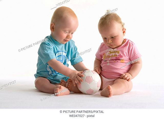 Two toddlers playing with a ball