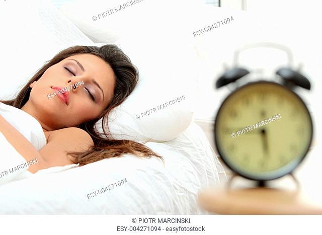 Beautiful Caucasian woman and alarmclock
