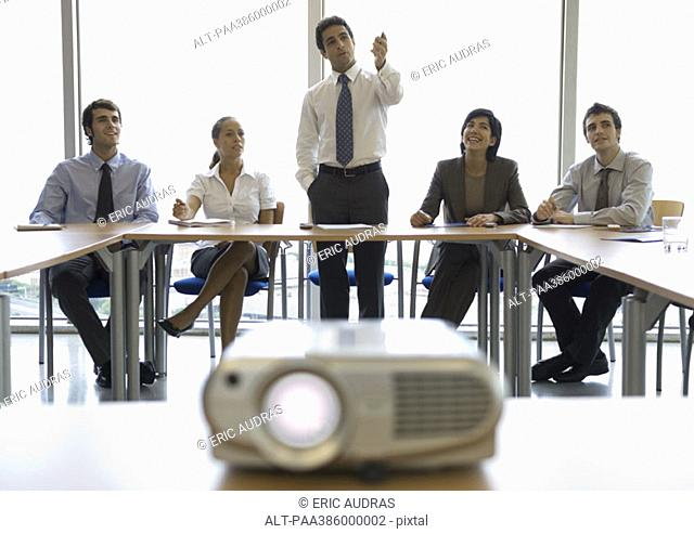 Businesspeople watching presentation, videoprojector in foreground