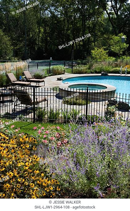 SWIMMING POOLS:Flower bed of Russian sage, brown eyed susans, roses in foreground , fenced pool area with hot tub, chaise lounges , tennis court beyond