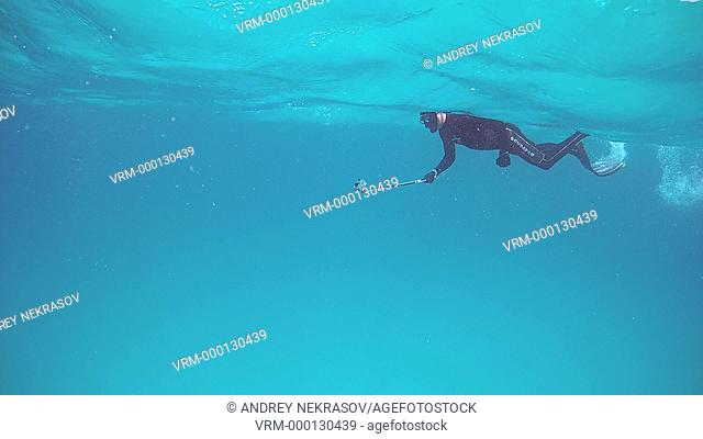 Freediver swims on the water surface taking on action camera, Indian Ocean, Maldives