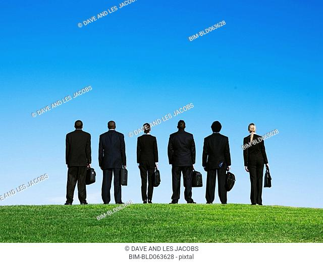 Business people standing outdoors in grass with briefcases