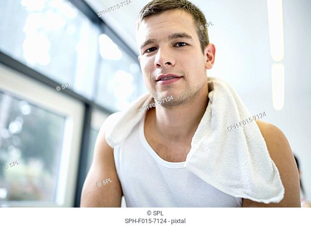 MODEL RELEASED. Portrait of young man with towel around neck in gym, close-up