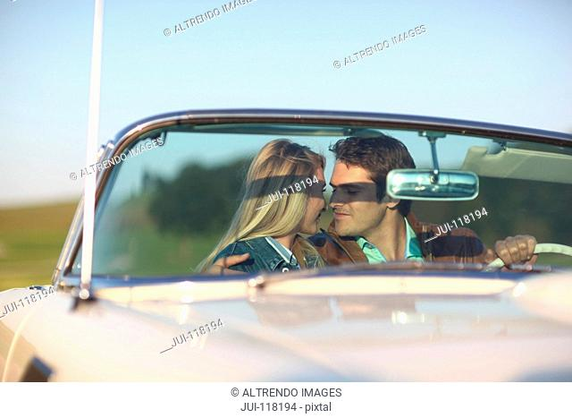 Romantic Couple Driving On Country Road In Open Top Car
