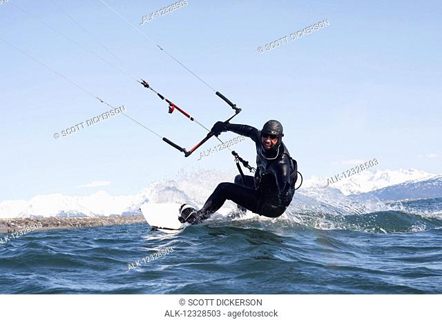 Man kitesurfing with Kenai Mountains in the background, Homer, South-central Alaska; Homer, Alaska, United States of America