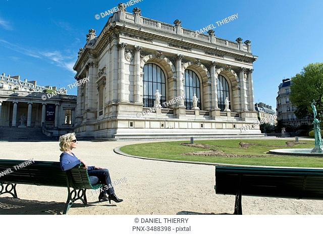 France. Paris 16th district. Woman sitting on a bench in front of the Galliera palace, the Museum of Fashion of the City of Paris