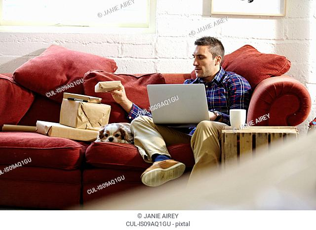 Mid adult man preparing parcels on sofa in picture framers showroom