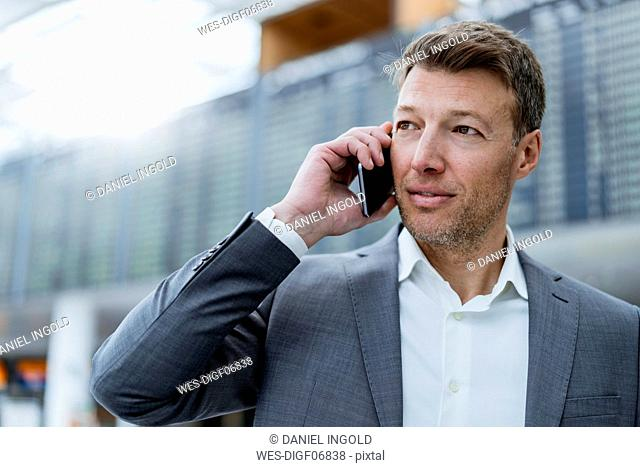 Portrait of businessman on cell phone at the airport