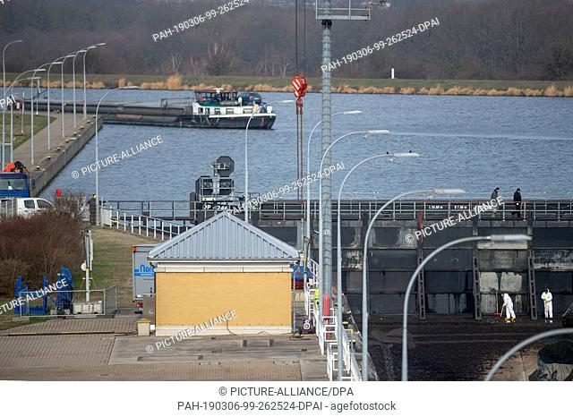 06 March 2019, Saxony-Anhalt, Magdeburg: Workers walk over a table weir which was built as a revision closure in front of the upper gate of the Rothensee lock