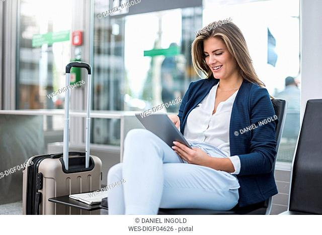 Young businesswoman with luggage sitting at waiting area using tablet