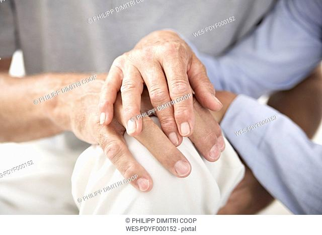Spain, Senior couple holding hands, close up